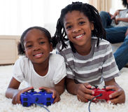 Plan rapproché des enfants de mêmes parents jouant le jeu vidéo Photo libre de droits