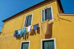 Plan rapproché des fenêtres sur les murs colorés et les vêtements accrochant dans une allée dans Burano Images stock