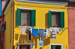 Plan rapproché des fenêtres sur les murs colorés et les vêtements accrochant dessus, dans Burano Images stock