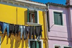 Plan rapproché des fenêtres sur les murs colorés et les vêtements accrochant le jour ensoleillé dans Burano Photographie stock