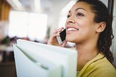 Plan rapproché des fichiers de recopie de femme d'affaires tout en à l'aide du téléphone portable dans le cafétéria Photo libre de droits