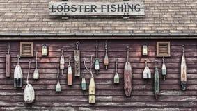 Plan rapproché des flotteurs colorés accrochant en dehors d'un cottage du ` s de pêcheur de homard Photographie stock