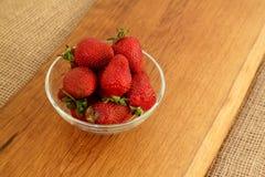 Plan rapproché des fraises fraîches dans le bol en verre du plat en bois Dessert rustique de style image stock