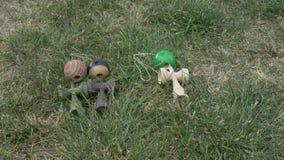 Plan rapproché des garçons choisissant chaque un jouet de kendama de l'herbe pour jouer - banque de vidéos