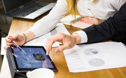 Plan rapproché des gens d'affaires à l'aide de la tablette dans le bureau image stock