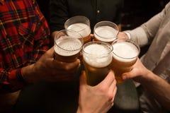 Plan rapproché des hommes grillant avec de la bière Photos stock