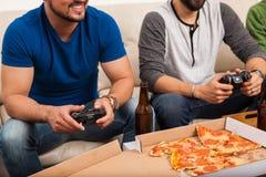 Plan rapproché des hommes jouant des jeux vidéo Images stock