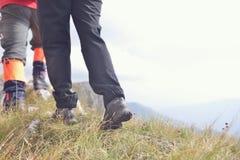 Plan rapproché des jambes de jeunes randonneurs marchant sur le chemin de pays Jeune réveil de traînée de couples Foyer sur augme Image stock