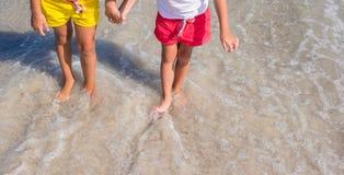 Plan rapproché des jambes de petites filles sur la plage tropicale Images stock