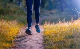 Plan rapproché des jambes du ` un s d'athlète dans les leggins noirs et l'espadrille noire Photos libres de droits