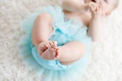 Plan rapproché des jambes et des pieds du bébé sur la jupe de port de tutu de turquoise de fond blanc photo libre de droits