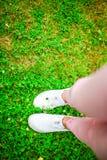 Plan rapproché des jambes femelles dans des espadrilles sur l'herbe dehors en parc Photo stock