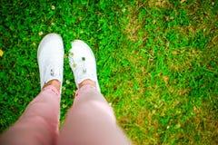 Plan rapproché des jambes femelles dans des espadrilles sur l'herbe dehors en parc Photos libres de droits