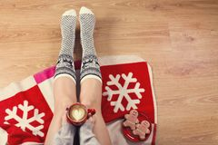 Plan rapproché des jambes femelles dans les chaussettes chaudes avec des cerfs communs, des cadeaux de Noël, un papier d'emballag Image stock