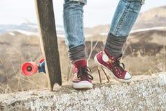 Plan rapproché des jambes femelles dans les jeans et des espadrilles élégantes à côté d'un longboard ou d'une planche à roulettes Image stock