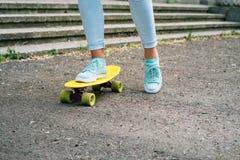 Plan rapproché des jambes femelles dans les jeans et des espadrilles montant un skateboar Images libres de droits