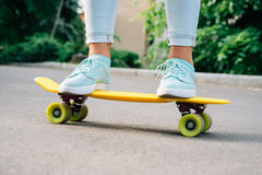 Plan rapproché des jambes femelles dans les jeans et des espadrilles se tenant sur un hurlement Photos stock