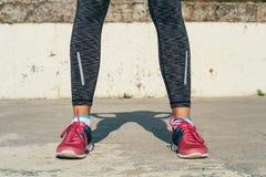 Plan rapproché des jambes femelles sportives dans des espadrilles rouges sur un p concret Images stock