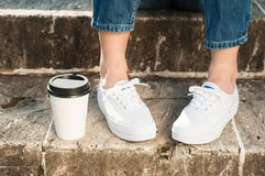 Plan rapproché des jeans et des espadrilles de port de femme tenant le coffe proche Photos stock