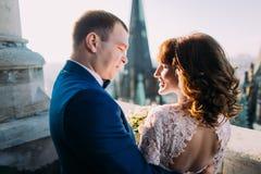 Plan rapproché des jeunes mariés heureux étreignant sur le balcon gothique antique de cathédrale Photographie stock libre de droits