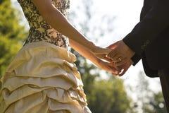 Plan rapproché des jeunes mariés se faisant face tenant des mains Photo libre de droits
