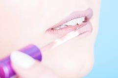 Plan rapproché des lèvres avec la brosse appliquant les lipgloss brillants Photo libre de droits