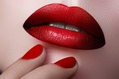 Plan rapproché des lèvres de la femme avec le maquillage et la manucure de mode beau Image stock