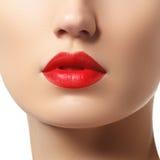 Plan rapproché des lèvres du ` s de femme avec le maquillage brillant rouge de mode lumineuse Images stock