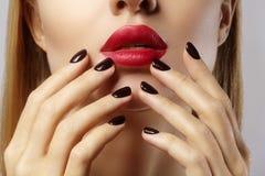 Plan rapproché des lèvres du ` s de femme avec le maquillage et la manucure rouges de mode Belles pleines lèvres femelles avec le Photo stock