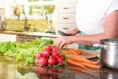 Plan rapproché des légumes de coupe de femme dans la cuisine ensoleillée Photographie stock libre de droits
