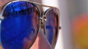 Plan rapproché des lunettes de soleil sur le visage de la fille et la réflexion de la piscine dans les verres clips vidéos