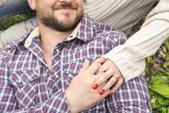 Plan rapproché des mains étreignant des couples de type et de son amie Images stock