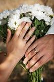 Plan rapproché des mains avec des boucles de mariage Photo stock