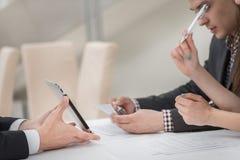 Plan rapproché des mains avec le comprimé et l'ordinateur portable Hommes d'affaires sur des corpus Images stock