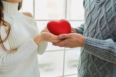 Plan rapproché des mains avec un coeur d'un couple affectueux Photographie stock libre de droits