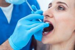 Plan rapproché des mains d'un dentiste nettoyant les dents d'une jeune femme photographie stock libre de droits