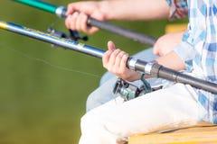 Plan rapproché des mains d'un garçon avec une canne à pêche Images stock