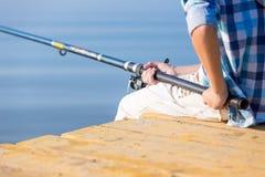 Plan rapproché des mains d'un garçon avec une canne à pêche Photo libre de droits