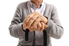 Plan rapproché des mains d'un homme plus âgé sur la canne de marche Photos stock