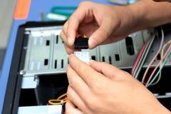 Plan rapproché des mains d'un technicien câblant un mainboard Photos libres de droits