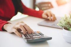 Plan rapproché des mains d'une femme d'affaires utilisant l'ordinateur portable et du compte sur la calculatrice photo libre de droits