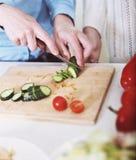 Plan rapproché des mains d'une femme faisant cuire la salade de légumes Photographie stock