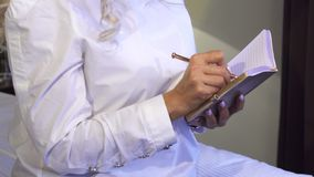 Plan rapproché des mains d'une femme qui fait des notes dans son carnet image libre de droits