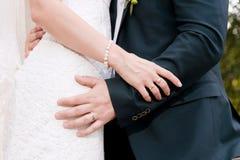Plan rapproché des mains dans les étreintes des nouveaux mariés le jour du mariage Photos libres de droits