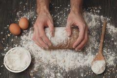 Plan rapproché des mains de boulanger du ` s des hommes sur le pain noir avec la poudre de farine Cuisson et concept de pâtisseri photo libre de droits
