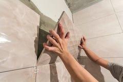 Plan rapproché des mains de carreleur de travailleur installant les carreaux de céramique beiges légers sur des murs de la future images libres de droits