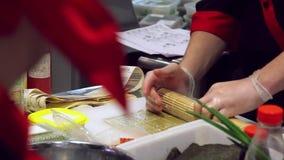 Plan rapproché des mains de chef dans les gants roulant vers le haut des sushi clips vidéos