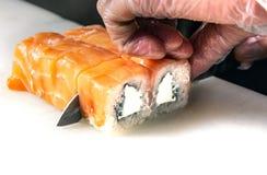 Plan rapproché des mains de chef roulant vers le haut des coupes de sushi dans des parties sur la cuisine image libre de droits