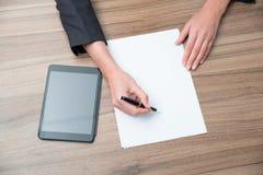 Plan rapproché des mains de femme d'affaires tout en notant de l'information essentielle Images stock