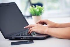 Plan rapproché des mains de femme fonctionnant avec l'ordinateur portable Photographie stock libre de droits